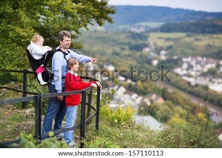 Young active father, his son and baby daughter in a back carrier enjoying a beautiful view from an observation deck during a hike in a scenic German mountain landscape - stock photo