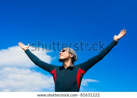 young active man standing on the background of blue sky - stock photo