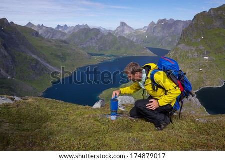 Young active man with backpack hiking on Lofoten islands in Norway on sunny day with scenic panorama in the background - stock photo
