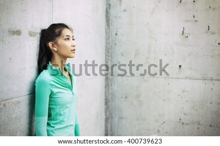 Young active woman leaning against wall  - stock photo
