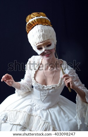 young actress in a white wig holding a theatrical mask - stock photo