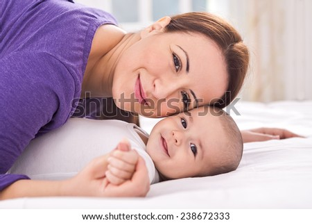 Young adorable mother with baby - stock photo