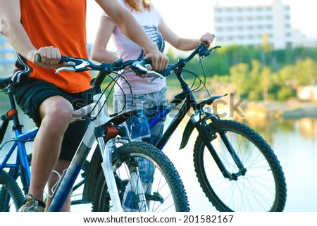 young adult activity Couple friends in shirt of two bicyclists on brink rock looks at  summer sunset sky, hotel building background in love ride bicycles on beach horizon No face Unrecognizable person - stock photo