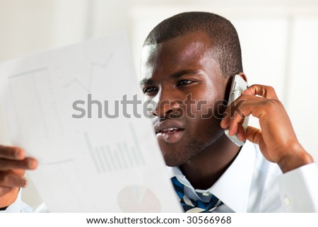 young adult afro-american businessman examining charts and talking on the phone - stock photo