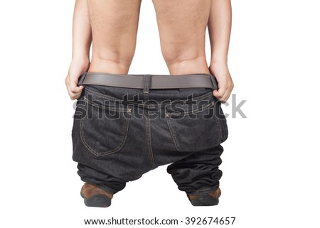 Young adult asian man pulls up his dark jeans, rear view, close-up studio. Isolate on white background - stock photo