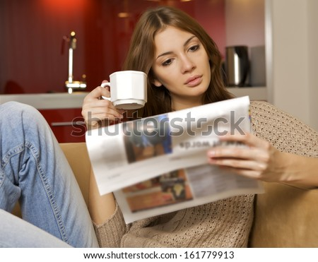 young adult beautiful brunette woman drinking coffee and reading newspaper in luxury apartment - stock photo