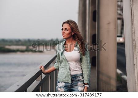 young adult beautiful  fashion woman standing on bridge  - stock photo