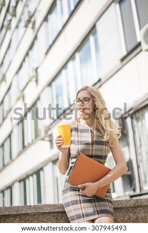 Young adult , beautiful sexy woman business hold in hand coffee cup in the fresh air sitting on the stairs against office building, laptop lie on legs. Sexual blond businesswoman look at far away  - stock photo
