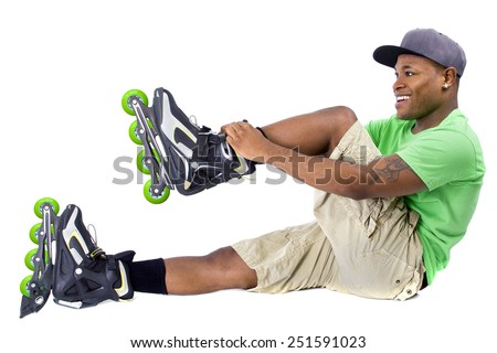 young adult black man posing with rollerblade skates - stock photo