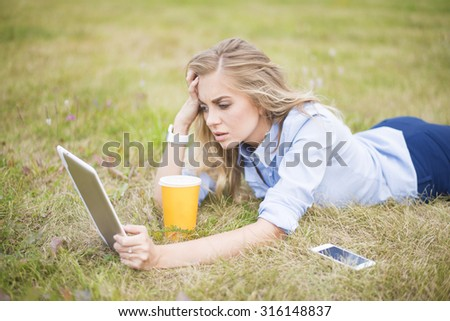young adult blond caucasian business Woman using digital tablet computer in city park Businesswoman lie on summer fresh green grass outdoor Coffee cup and mobile cell phone stand near - stock photo