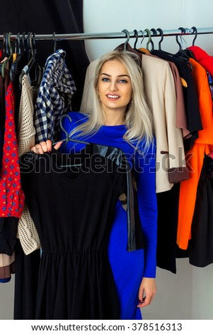 Young adult blonde woman smiling and choosing a dress in clothing store. Happy young lady with a lot of clothes. Shopping concept. - stock photo
