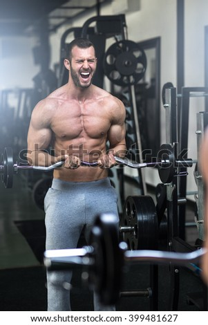 Young adult bodybuilder doing weight lifting in gym while screaming - stock photo