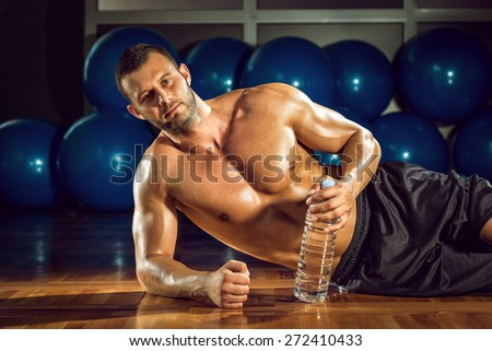 Young adult bodybuilder taking relax lying on gym floor. - stock photo