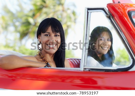 young adult brunette twin women driving convertible red car and looking at camera. Horizontal shape, side view - stock photo