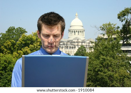 Young adult business man using a laptop computer in front of a state capitol building. - stock photo