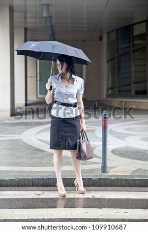 young adult businesswoman on the street under the rain - stock photo