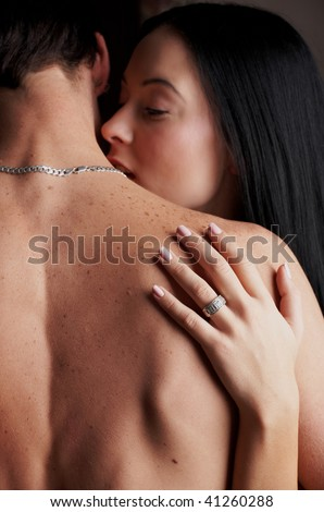 Young adult Caucasian couple in passionate embrace during sexual foreplay - stock photo