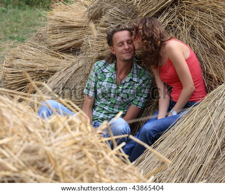 Young adult caucasian couple laughing and playfully sitting in hay - stock photo