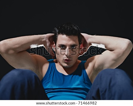young adult caucasian male in blue sportswear exercising abdominals on black background, looking at camera. Horizontal shape, front view, copy space - stock photo