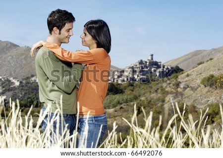 young adult couple embracing in the countryside - stock photo