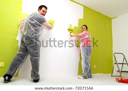 Young adult couple painting interior wall of house - stock photo