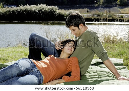 Young adult couple relaxing near a lake - stock photo