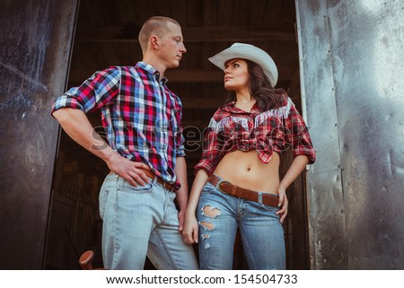 young adult couple standing near stable, closeup photo - stock photo