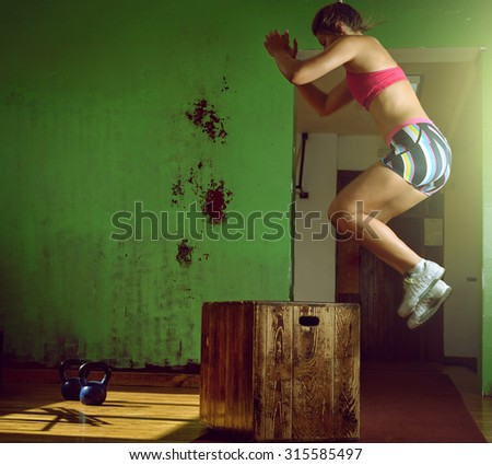 Young adult crossfit girl jumping on box in gym club. - stock photo