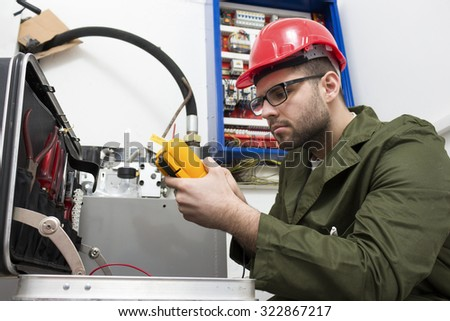 young adult electrician builder engineer worker in front of fuse switch board - focus on hand - stock photo