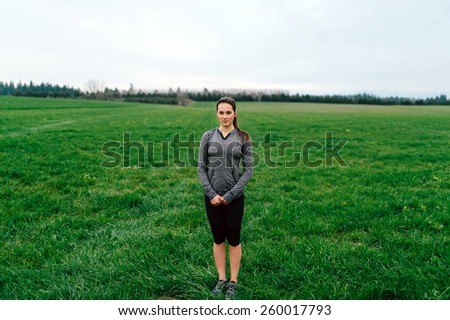 Young Adult Female standing in grass field - stock photo