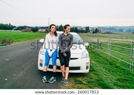 Young Adult Females resting on car after run - stock photo