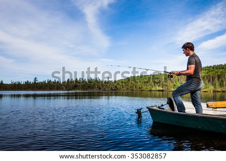 Young Adult Fishing trout from a deck in a calm Lake during the morning - stock photo