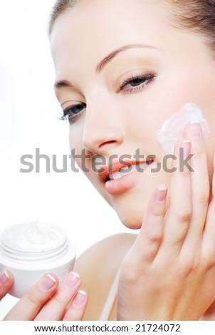 Young adult girl applying moisturiser cream on cheek. Healthcare concept. - stock photo