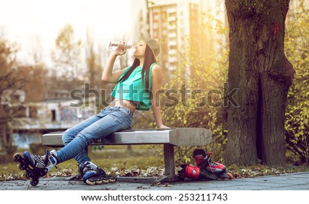 Young adult girl with roller blades drinking bottled water whlie relaxing on bench. - stock photo
