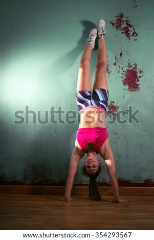 Young adult gymnastic fit girl is standing on hands next to a wall - stock photo