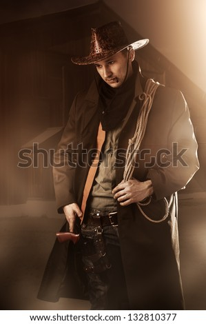 Young adult handsome man in cowboy clothes - stock photo