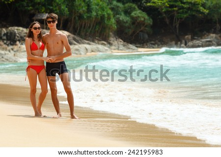 young adult happy couple in sunglasses on the beach - stock photo