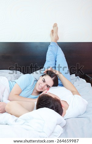 Young adult heterosexual smiling couple in love lying on bed in bedroom at morning,  while pretty woman looking at good looking man. Lifestyle concept photo in domestic atmosphere, peacefull life. - stock photo