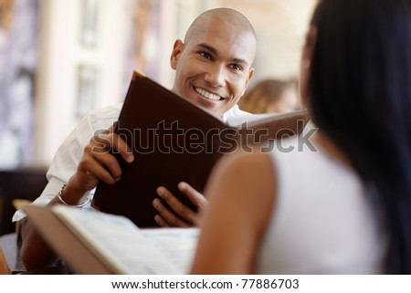 young adult hispanic couple dining out in restaurant and reading menu. Horizontal shape, waist up, focus on background - stock photo