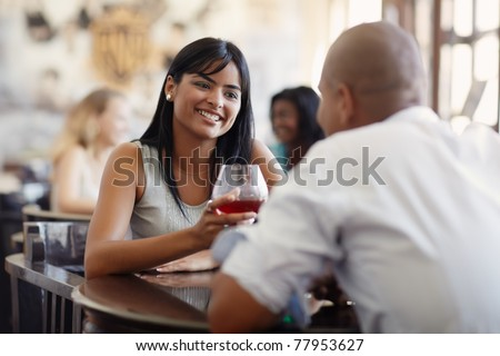 young adult hispanic couple dining out in restaurant and toasting with cocktails. Horizontal shape, front view, focus on background - stock photo