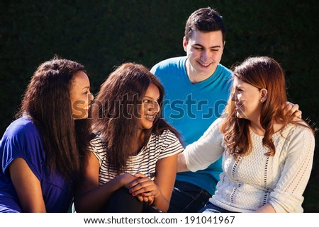 Young adult interracial group of friends talking and laughing  - stock photo