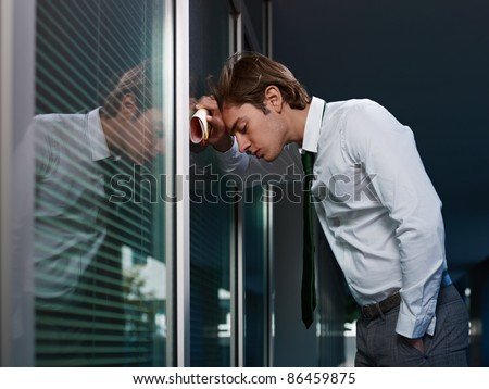 young adult italian business man banging his head against a window in office. Horizontal shape, copy space - stock photo