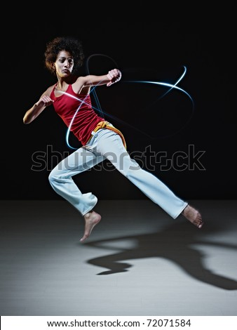 young adult latin american female doing capoeira flying kick in gym, with streaks of led lights all around. Vertical shape, full length, front view, copy space - stock photo