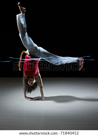 young adult latin american female handstanding and doing capoeira kick in gym, with streaks of led lights on waist. Vertical shape, full length, front view, copy space - stock photo