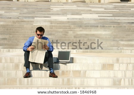 Young adult male reading a newspaper on steps with a laptop computer next to him. - stock photo