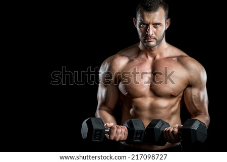 Young adult man doing barbell press in gym. Black background. Gym training workout. - stock photo