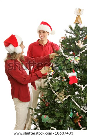 Young adult man home for Christmas is helping his mother decorate the tree.  Isolated on white. - stock photo