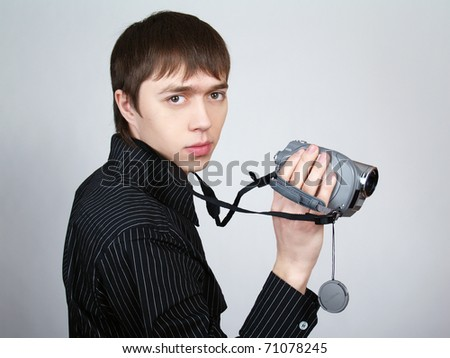 Young adult man in black shirt holding an HD camcorder - stock photo