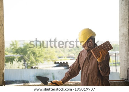 Young adult mason wearing brown stripped shirt holding red brick with holes and trowel on concrete wall and street background Unrecognizable person - stock photo