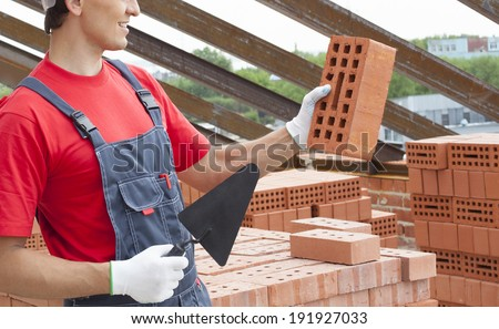 Young adult mason wearing overall holding brick and trowel on metal beam roof and sky background Unrecognizable person in blue and red uniform on brick stack backdrop No face - stock photo